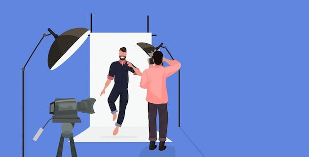 Photographe professionnel à l'aide d'un appareil photo homme tirant un homme barbu dans des vêtements décontractés posant un studio photo moderne horizontal pleine longueur