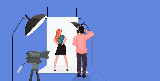 Photographe professionnel à l'aide de caméra homme tir belle belle femme rousse sexy modèle posant dans un studio photo moderne horizontal pleine longueur