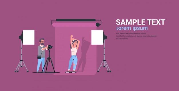 Photographe professionnel à l'aide de caméra homme tir belle femme sexy modèle posant dans un studio photo moderne intérieur horizontal pleine longueur plat