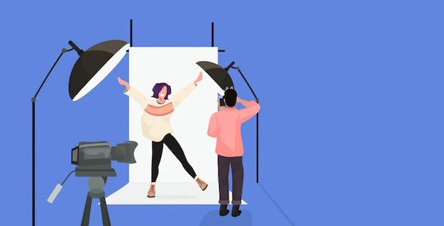 Photographe professionnel à l'aide de caméra homme tir belle modèle de femme sexy levant les mains posant dans un studio photo moderne horizontal