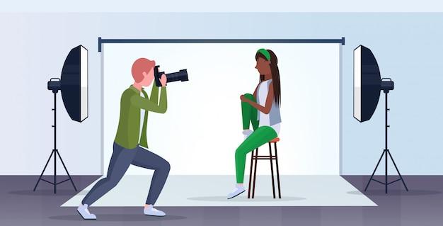 Photographe professionnel à l'aide de caméra homme tir belle modèle de femme sexy posant intérieur moderne studio photo horizontal pleine longueur