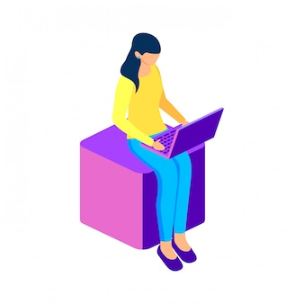 Pigiste femme travaillant avec un ordinateur portable assis sur un cube