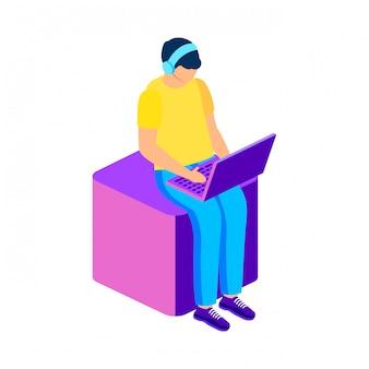 Pigiste travaillant avec un ordinateur portable assis sur un cube