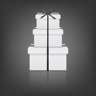 Pile de trois coffrets cadeaux blancs réalistes avec ruban noir et arc