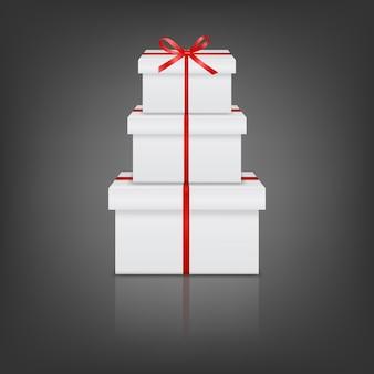 Pile de trois coffrets cadeaux blancs réalistes avec ruban rouge et arc