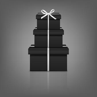 Pile de trois coffrets cadeaux noirs réalistes avec ruban blanc et arc