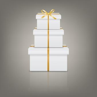 Pile de trois coffrets cadeaux réalistes blancs avec ruban doré et noeud