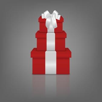 Pile de trois coffrets cadeaux rouges réalistes avec ruban blanc et arc