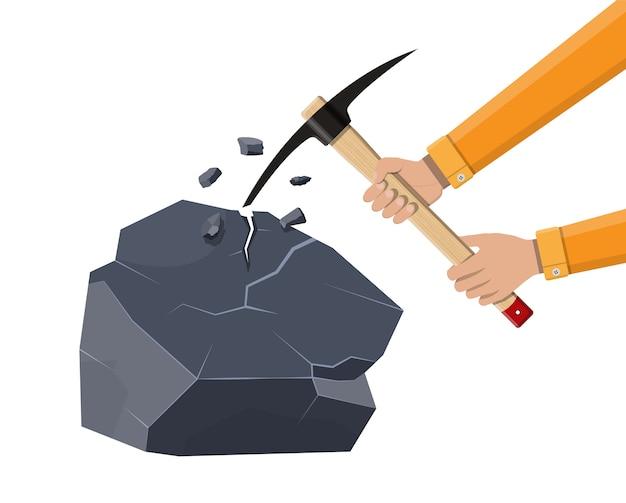 Pioche en bois avec pointe en fer et roche.