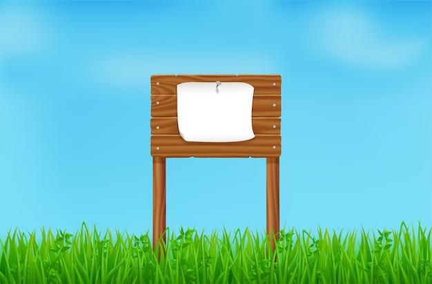 Planche de bois avec feuille blanche épinglée sur champ vert ou pelouse