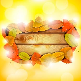 Planche de bois avec des feuilles d'automne colorées