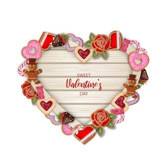 Planche de bois en forme de coeur avec des bonbons et des bonbons de la saint-valentin
