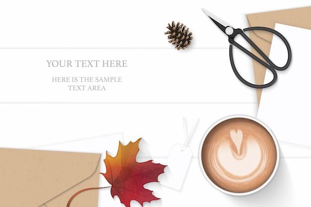 Plat laïque vue de dessus élégante composition blanche lettre kraft enveloppe de papier cône de pin café tag automne feuille d'érable ciseaux en métal vintage sur fond de bois.