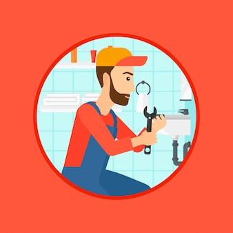 Plombier fixant le tuyau de l'évier avec une clé.