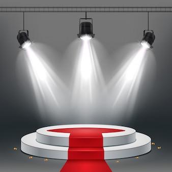 Podium blanc et tapis rouge éclairés par des projecteurs
