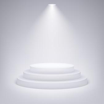Podium rond éclairé par des projecteurs sur fond gris.