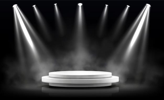 Podium rond, scène vide éclairée par des projecteurs.