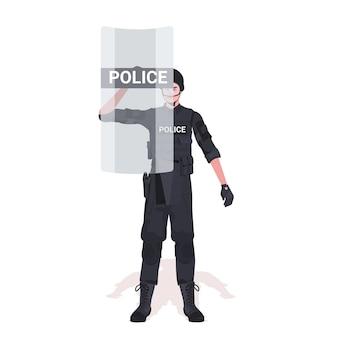 Policier en tenue tactique complète agent de police anti-émeute avec bouclier et manifestants