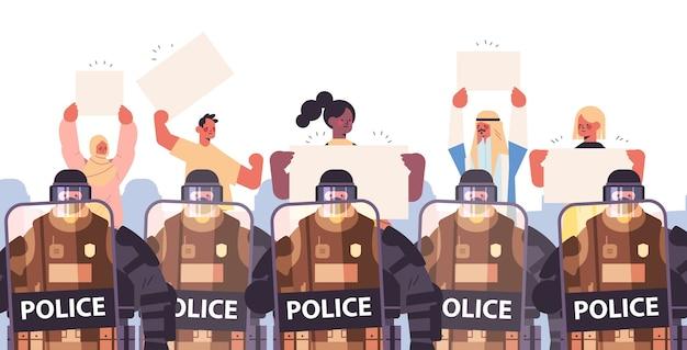 Les policiers en tenue tactique complète des agents de police anti-émeute contrôlant les manifestants de rue mix race avec des pancartes lors des affrontements de manifestation