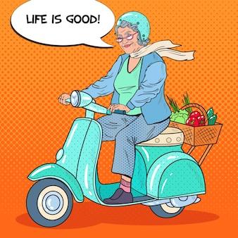 Pop art happy senior woman riding scooter avec panier de légumes