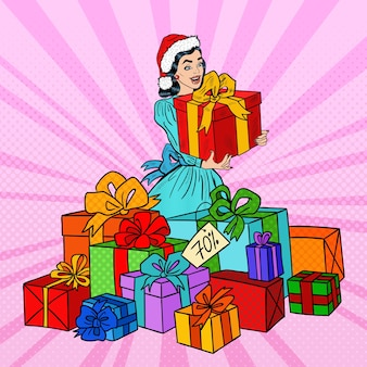 Pop art happy woman in santa hat avec de grandes coffrets cadeaux en vente de noël.