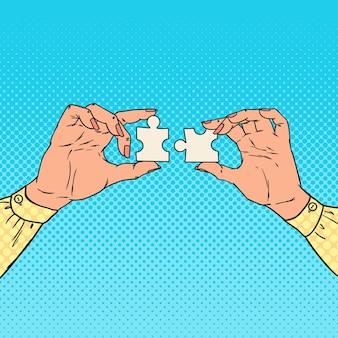 Pop art mains féminines tenant deux pièces de puzzle. concept de solution d'entreprise.