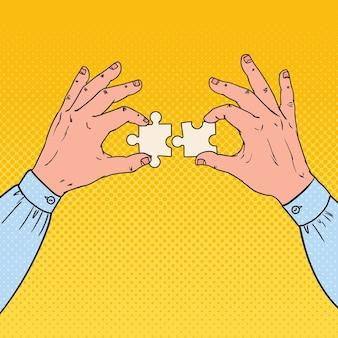 Pop art mains mâles tenant deux pièces de puzzle. concept de solution d'entreprise.