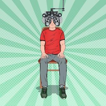 Pop art man patient à la clinique d'optométrie avec phoroptère optique