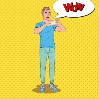 Pop art surpris homme faisant de la vidéo sur smartphone. adolescent guy prendre une photo sur téléphone mobile.
