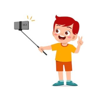 Pose mignonne de petit garçon d'enfant et selfie devant la caméra