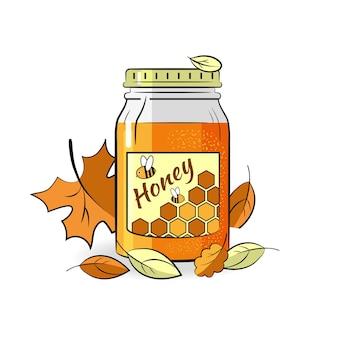 Pot en verre avec du miel entouré de feuilles d'automne.