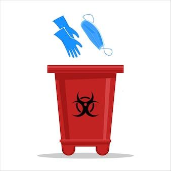 Poubelle rouge avec le signe de danger biologique pour les gants en latex et les masques chirurgicaux usagés