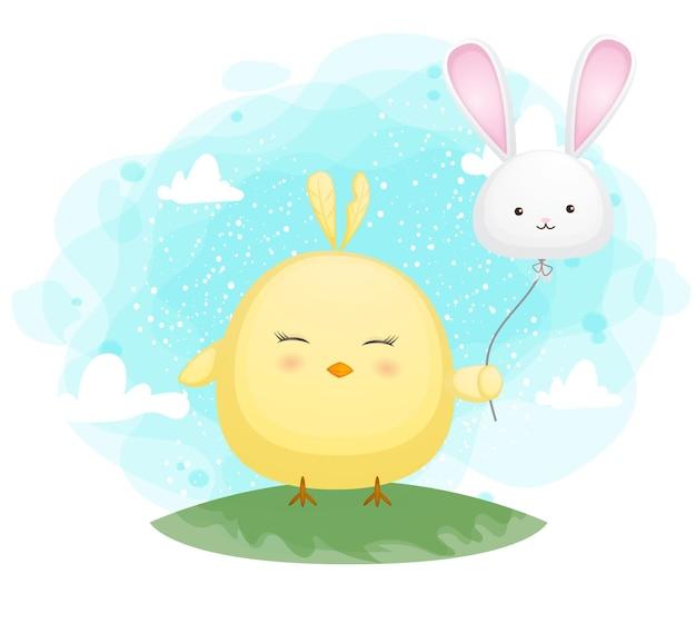 Poussins souriants mignons tenant un ballon de lapin
