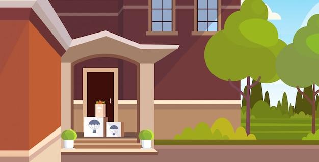 Produits d'épicerie parsels boîtes en carton sous la porte d'entrée air mail express concept de livraison postale maison moderne bâtiment extérieur horizontal