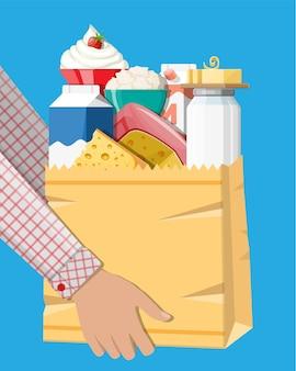 Produits laitiers mis dans un sac à provisions en papier avec du fromage, du cottage et du beurre. produits laitiers. produits frais traditionnels de la ferme. illustration vectorielle dans un style plat