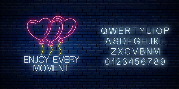 Profitez de chaque instant - phrase d'inscription au néon brillant avec des ballons en forme de coeur sur un mur de briques sombres avec alphabet.