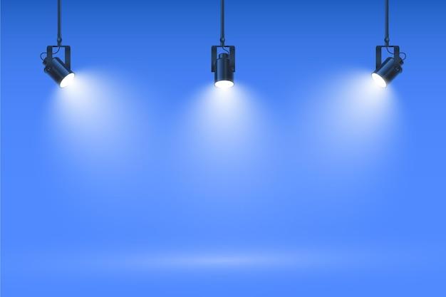 Projecteurs sur fond de mur bleu studio