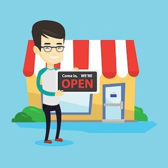 Propriétaire de magasin asiatique tenant enseigne ouverte.