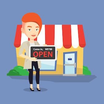 Propriétaire de magasin femme tenant enseigne ouverte.