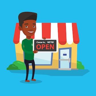 Propriétaire de magasin tenant enseigne ouverte.