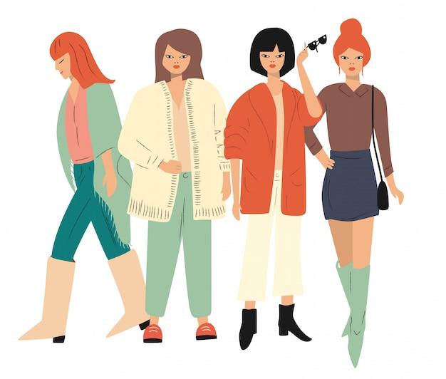 Quatre jeunes femmes en vêtements d'automne debout et marchant. isolé sur blanc appartement
