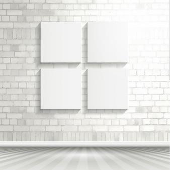 Quatre toiles vierges sur un mur de briques blanches