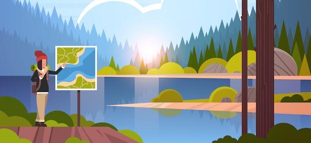 Randonnée touristique femelle avec sac à dos à la recherche de carte de voyage femme voyageur planification itinéraire randonnée concept lever du soleil paysage nature rivière forêt montagnes