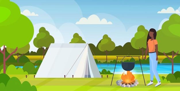Randonneur femme préparant de la nourriture dans un pot bouillant melon au feu de camp randonnée concept afro-américain voyageur sur tente de randonnée camping paysage fond pleine longueur plat horizontal