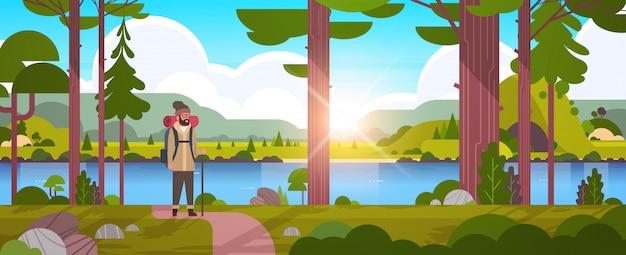 Randonneur touriste mâle avec sac à dos homme voyageur tenant bâton debout dans la forêt randonnée concept lever du soleil paysage nature rivière montagnes