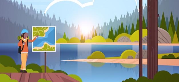 Randonneuse touristique avec sac à dos à la recherche de carte de voyage femme voyageur planification itinéraire randonnée concept paysage nature rivière forêt montagnes fond horizontal pleine longueur