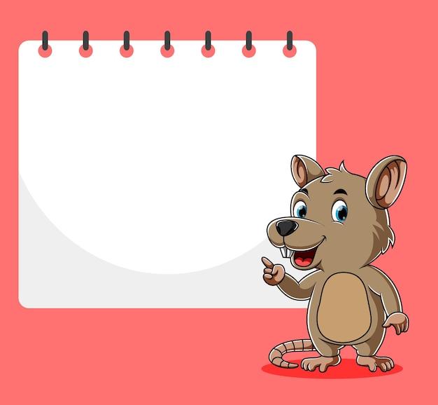 Le rat debout et pointant le papier vierge à côté de lui