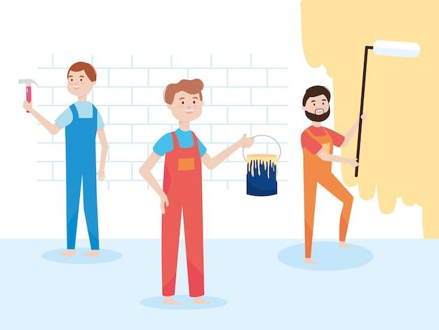 Rénovation du mur des travailleurs d'équipe avec un rouleau à peinture, un seau et un marteau.