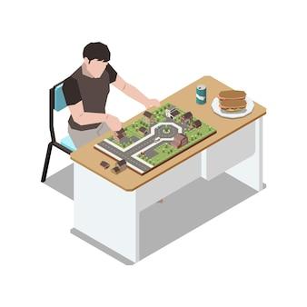Restez à la maison composition isométrique avec un homme assis à table jouant avec un petit modèle d'illustration de la ville