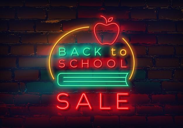 Retour à l'école enseigne au néon sur fond de mur de briques à vendre et à rabais